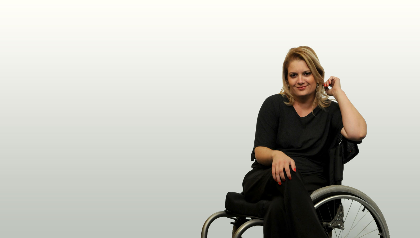 juliana in her wheelchair, she wears black and smiles