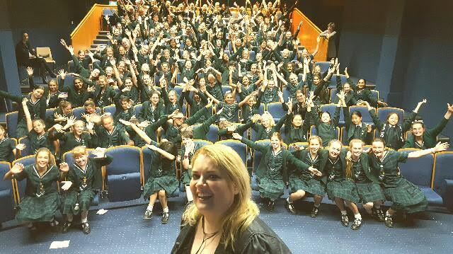 juliana at a stage in a school auditorium, she smiles and in the background 150 girl students have their arms up cheering
